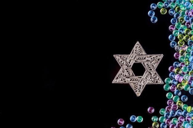 Estrela de david metálica. símbolo judeu em fundo preto.