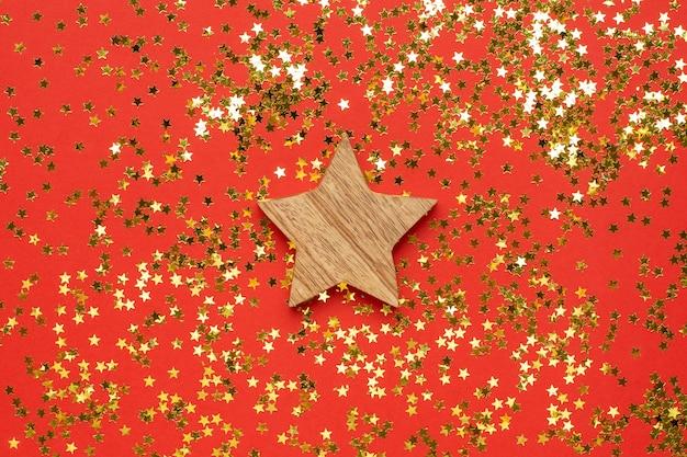 Estrela de decoração de madeira com confetes de estrelas douradas