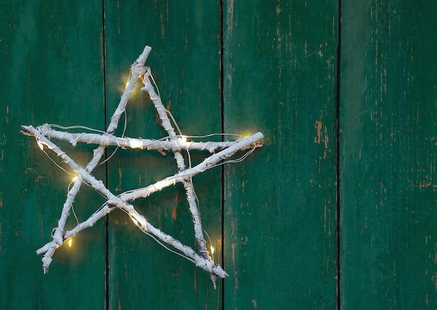 Estrela de galho caseiro de natal em fundo de madeira verde rústico