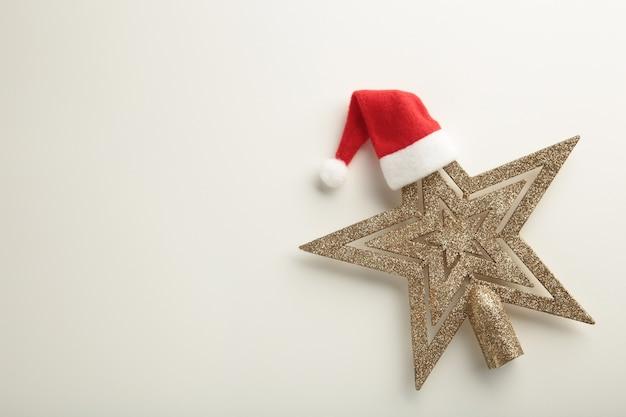 Estrela de natal com chapéu de papai noel em fundo branco. vista do topo