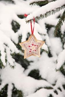 Estrela de natal, decoração na árvore do abeto, galhos de árvores, fundo de inverno natural ao ar livre verde