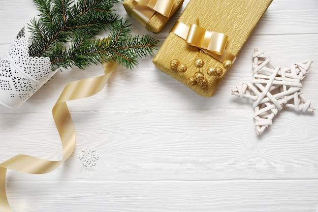 Estrela de natal e fita de presente de ouro, flatlay em um branco de madeira