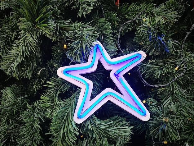 Estrela de néon iluminada azul decorada na árvore de natal verde