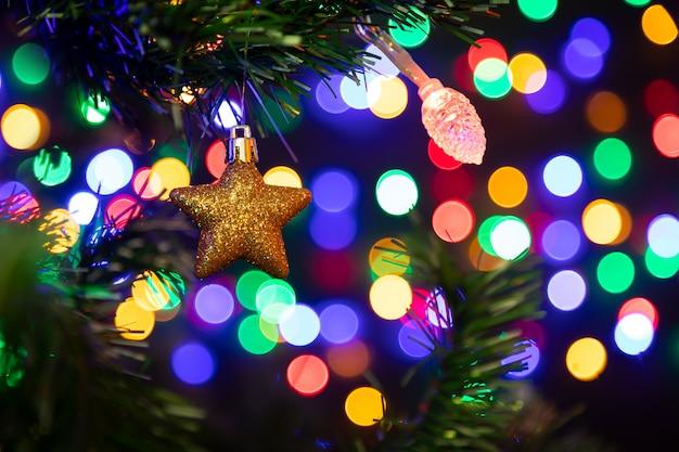 Estrela de ouro bola de natal pendurado em uma árvore de natal em segundo plano um monte de guirlandas brilhando em cores diferentes.