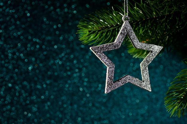 Estrela de prata em um galho de árvore de natal em um fundo azul brilhante de bokeh.