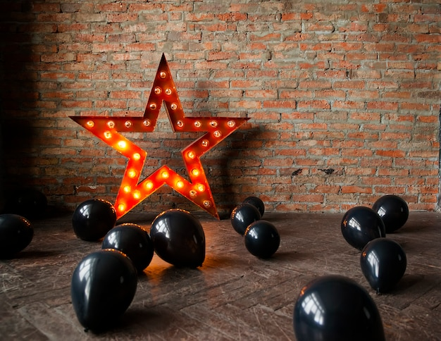 Estrela decorativa com lâmpadas e balões pretos no chão.