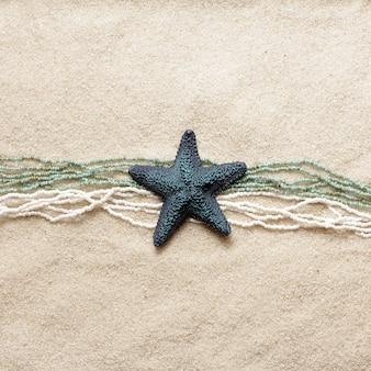 Estrela do mar azul com contas na areia brilhante do mar