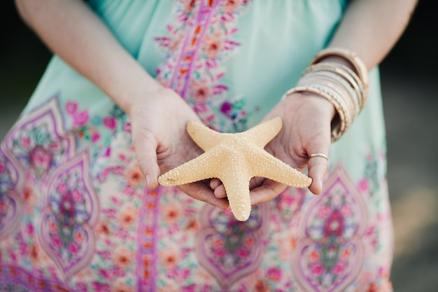 Estrela do mar branca nas mãos de uma garota