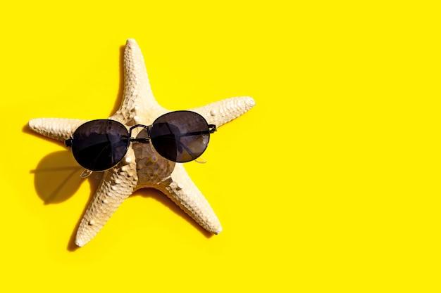 Estrela do mar com óculos de sol em fundo amarelo. aproveite o conceito de férias de verão.
