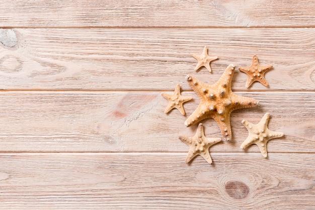 Estrela do mar, conchas do mar em uma mesa de madeira, vista superior, plana leiga com espaço de cópia.