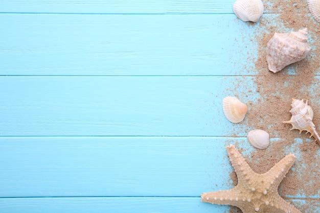 Estrela do mar e conchas do mar com areia em madeira. conceito de verão