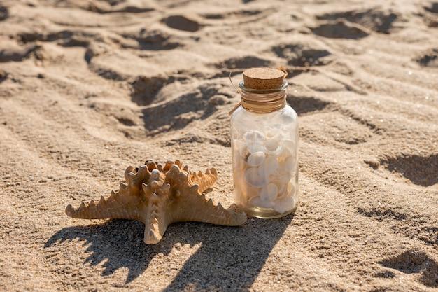 Estrela do mar e jarra de vidro com conchas na areia