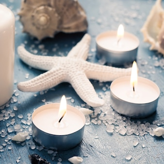 Estrela do mar e velas acesas sobre fundo vintage.