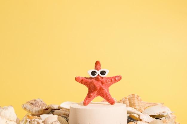 Estrela do mar em óculos de sol em um pedestal entre conchas em um conceito criativo de verão de fundo amarelo