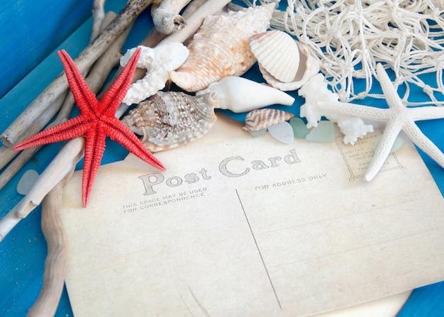 Estrela do mar, madeiras, rede, conchas e vidro amarrado na parede de madeira azul perto com espaço de cópia de cartão postal