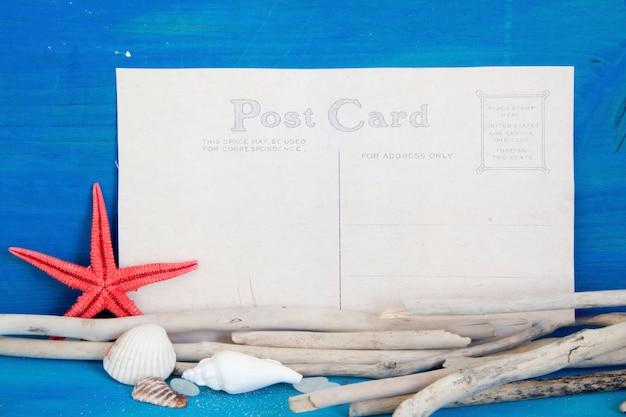 Estrela do mar, madeiras resistidas e conchas na vista superior da parede de madeira azul com espaço de cópia em papel