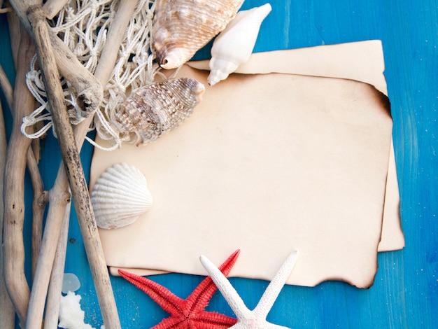 Estrela do mar, madeiras resistidas, rede e conchas na vista superior da parede de madeira azul com espaço de cópia em papel