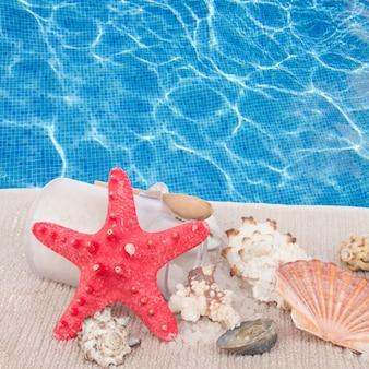 Estrela do mar vermelha com configuração de spa marinho no fundo da água azul