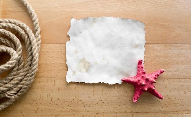 Estrela do mar vermelha deitada em um pedaço de papel em branco sobre placas de madeira