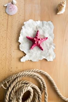 Estrela do mar vermelha deitada em um pedaço de papel velho em pranchas de madeira com conchas e corda