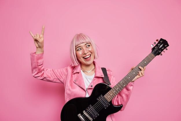 Estrela do rock alegre e enérgica mantém o braço levantado e faz sinal de heavy metal feliz por escrever seu próprio álbum com músicas populares tocando violão vestido com jaqueta