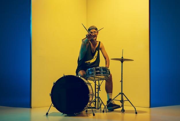 Estrela do rock. jovem músico com bateria tocando em fundo amarelo em luz de néon. conceito de música, hobby, festival, entretenimento, emoções. baterista alegre e inspirado. retrato colorido do artista.