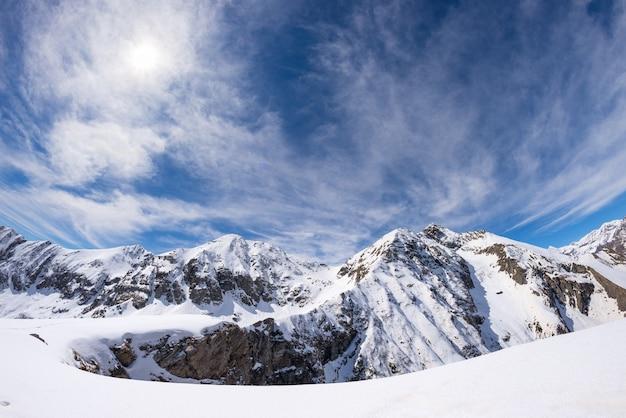 Estrela do sol brilhando sobre montanhas cobertas de neve, alpes italianos