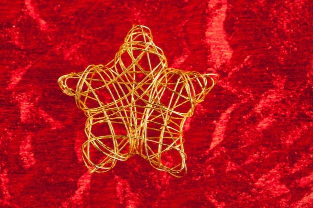 Estrela dourada de natal do fio sobre o vermelho