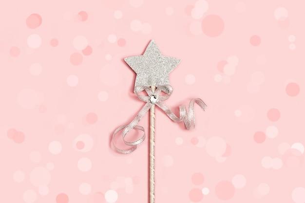 Estrela festiva de prata brilhante com lantejoulas em fundo rosa suave com decoração de enfeites.