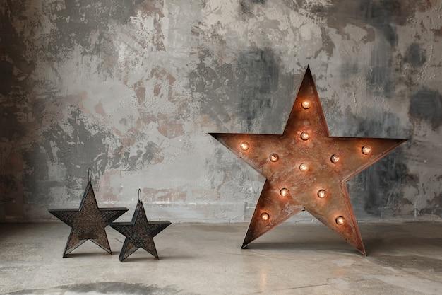 Estrela grande com luzes de bulbo e pequena no fundo do muro de cimento, decoração interior do sótão.