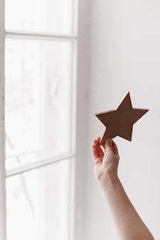 Estrela na mão de uma criança contra a janela