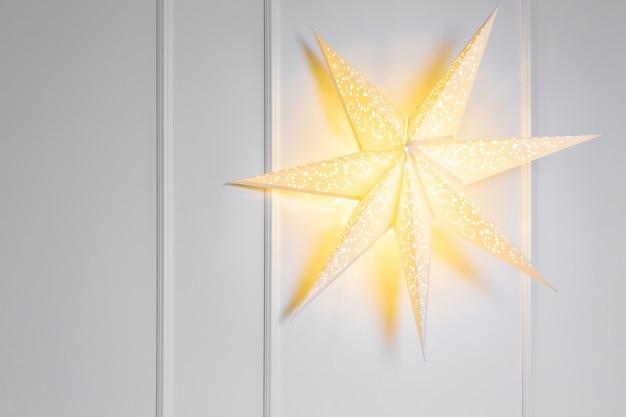 Estrela volumétrica brilhante em uma parede branca de fundo de ano novo ou natal cartão postal e cartão postal