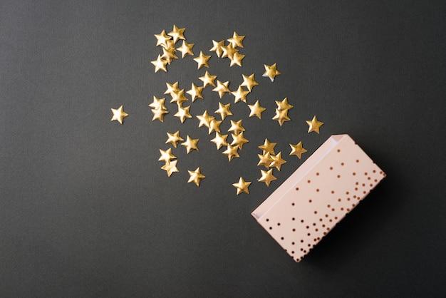 Estrelas amarelas cadentes da caixa de presente sobre a mesa preta