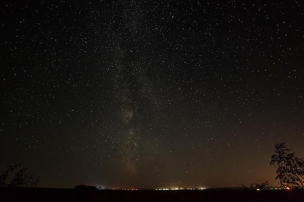 Estrelas brilhantes no céu noturno acima da cidade com iluminação pública