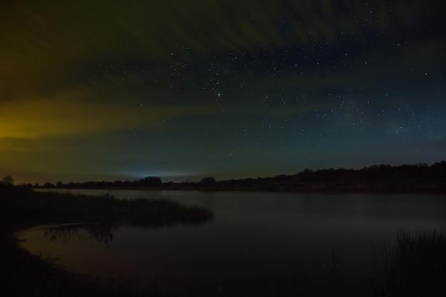 Estrelas brilhantes no céu noturno com nuvens do rio.