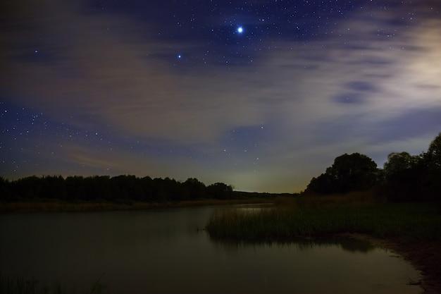 Estrelas brilhantes no céu noturno com nuvens no fundo do rio
