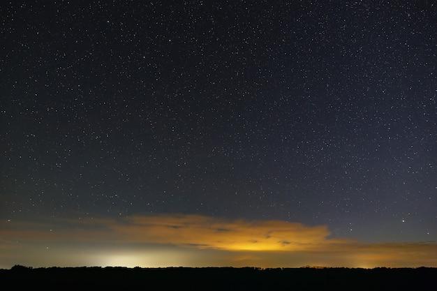 Estrelas da via láctea no céu à noite. espaço sideral e nuvens