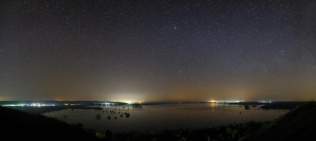 Estrelas da via láctea no céu antes do amanhecer. paisagem noturna com um lago. vista panorâmica do espaço estrelado.