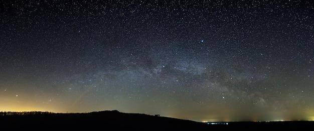 Estrelas da via láctea no céu noturno acima do horizonte. vista panorâmica do espaço estrelado.