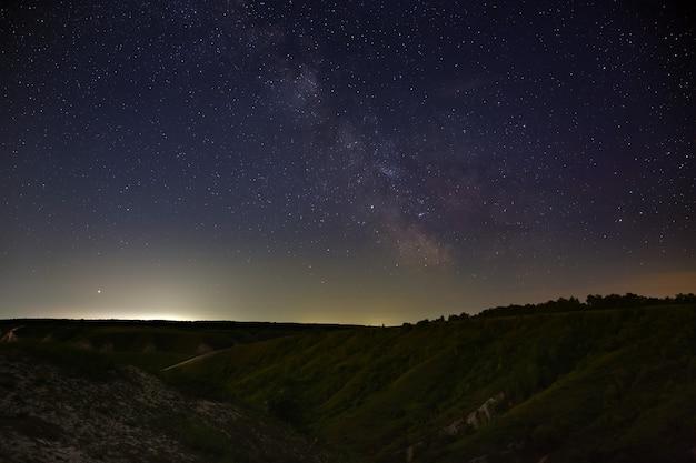 Estrelas da via láctea no céu noturno. uma vista do pôr do sol de fundo do espaço estrelado iluminou o horizonte.