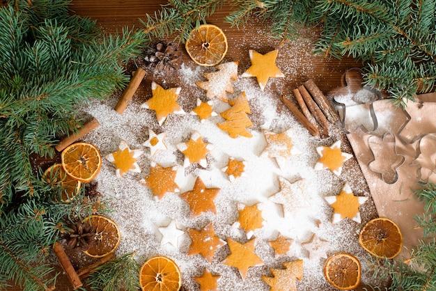 Estrelas de biscoitos caseiros de gengibre, decorado com açúcar de confeiteiro e rodeado por ramos de abeto e laranjas secas, canela.