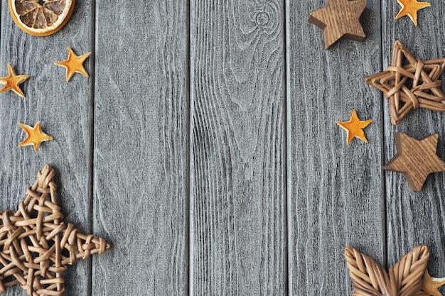 Estrelas de cascas de laranja secas, feitas de madeira e vime sobre um fundo cinza de madeira.