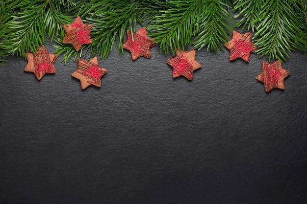 Estrelas de chocolate de biscoitos de natal caseiros com crunches de framboesa na mesa de ardósia com galhos de pinheiro