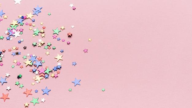 Estrelas de confete em fundo rosa com espaço de cópia
