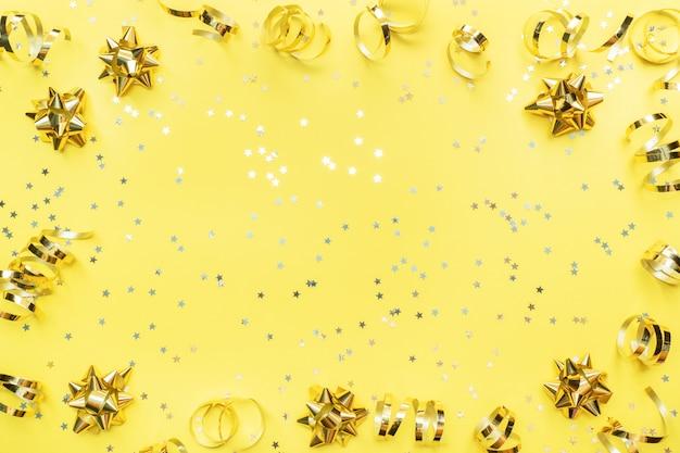 Estrelas de confetes ouro e fitas sobre um fundo amarelo. copie o espaço lay plana. cartão de felicitações para festa de aniversário, casamento dia das mães.