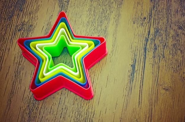 Estrelas de plástico de arco-íris no fundo de madeira