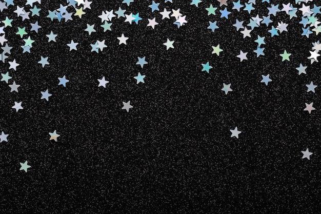 Estrelas de prata iridescente caindo confetes em fundo preto festivo