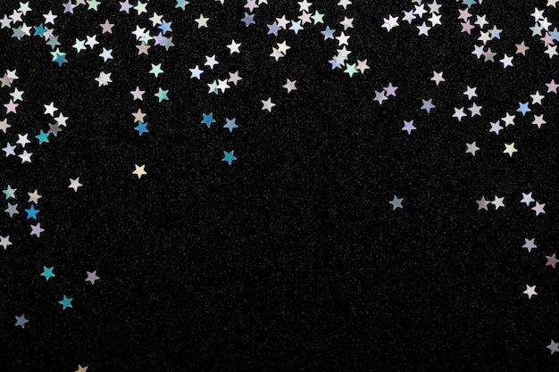 Estrelas de prata iridescente confetes em fundo preto festivo