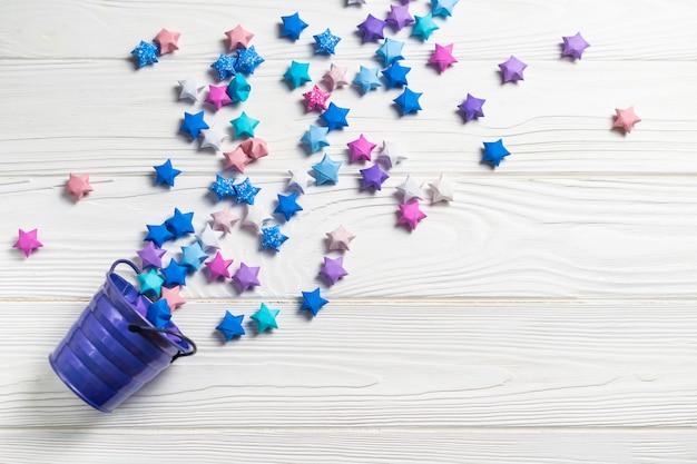 Estrelas de sorte de papel origami coloful folling fora do balde em madeira branca