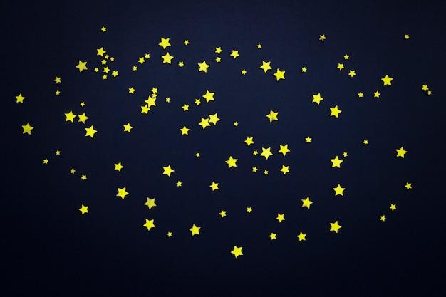 Estrelas decorativas em um fundo azul escuro. conceito do céu noturno